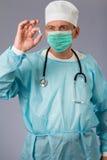 Médico con el estetoscopio y la mascarilla que sostienen una píldora GR imágenes de archivo libres de regalías