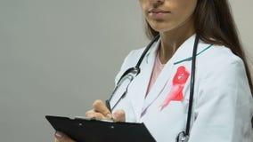 Médico con el tratamiento que prescribe de la cinta rosada, lucha contra cáncer de pecho almacen de video