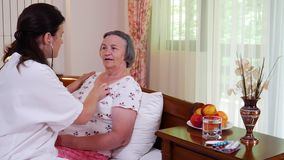 Médico de cabecera que comprueba a la mujer mayor que usa el estetoscopio en casa almacen de metraje de vídeo