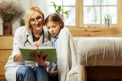 Médico de fascínio que lê um livro criançola com uma menina doente bonito imagens de stock