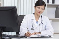 Médico de hospital chino de la mujer escritura en oficina Fotografía de archivo