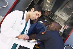Médico de hospital que toma a paramédicos de las notas Imagen de archivo libre de regalías
