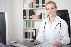 Médico de sexo femenino en su escritorio que mira la cámara Imagen de archivo