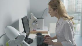 Médico de sexo femenino que trabaja en el ordenador metrajes