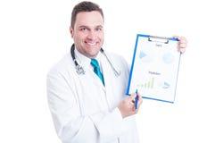Médico de sexo masculino que sonríe y que muestra estadísticas de la predicción sobre clipboar Foto de archivo