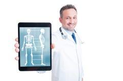Médico de sorriso que mostra o tela de computador do PC da tabuleta fotografia de stock