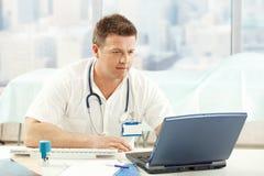 médico del Mediados de-adulto que trabaja con la computadora portátil Fotos de archivo