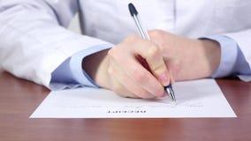 Médico diagnostique, las manos del doctor que escriben un recibo para la paciencia metrajes