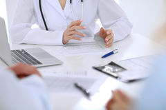 Médico e pacientes novos dos pares que discutem algo na tabela Entrega o close-up imagem de stock royalty free