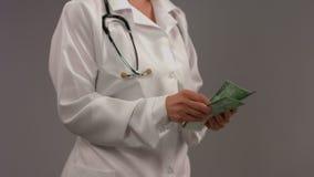 M?dico en la capa blanca que cuenta el dinero, sistema sanitario corrupto, medicina fotografía de archivo