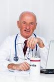 Médico en la práctica con el estetoscopio y la computadora portátil. Fotografía de archivo