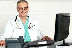 Médico envejecido con el estetoscopio alrededor de su cuello imágenes de archivo libres de regalías