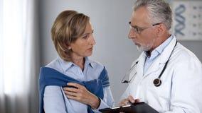 Médico envejecido que habla con el paciente femenino serio, mostrando resultados de la prueba, medicina imagenes de archivo