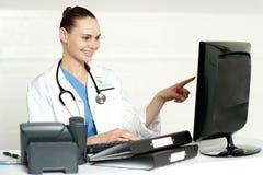 Médico especialista fêmea que aponta no ecrã de computador imagem de stock