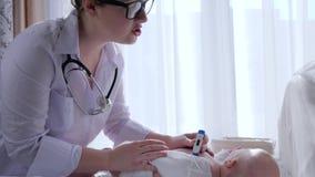 Médico examina, doctor con temperatura de las medidas del termómetro del cuerpo recién nacido en sitio ligero almacen de metraje de vídeo
