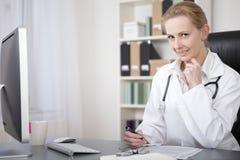 Médico fêmea em seus relatórios da escrita da tabela Imagens de Stock