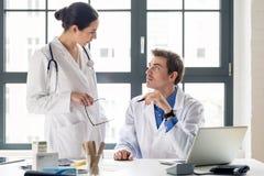 Médico fêmea novo que pede o conselho de seu miliampère experiente imagem de stock royalty free
