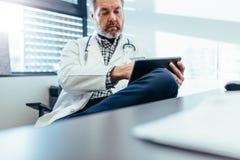 Médico facultativo que usa la PC de la tableta en su clínica fotos de archivo