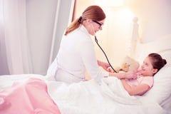 Médico geral de cabelo escuro que senta-se perto do doente bonito do sentimento da menina foto de stock
