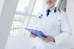 Médico geral maduro seguro com carta médica foto de stock