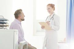 Médico geral que fala ao paciente imagem de stock royalty free