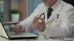Médico geral que procura a instrução pela droga nova no Internet, medicina vídeos de arquivo