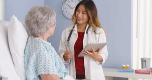 Médico japonês que fala com o paciente idoso na cama de hospital foto de stock