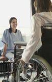 Médico Listening To Patient na cadeira de rodas foto de stock