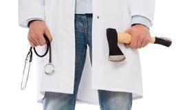 Médico mau que guarda um machado e um estetoscópio pequenos Fotografia de Stock Royalty Free