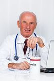 Médico na prática com estetoscópio e portátil. Fotografia de Stock