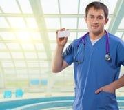 Médico positivo que mostra o cartão branco da visita que está em um b Fotografia de Stock Royalty Free