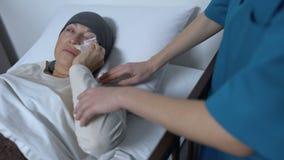 Médico que apoya terminal al paciente femenino de la enfermedad que limpia los rasgones en el lecho de enfermo, cuidado almacen de video