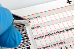 Médico que completa um formulário médico do diagnóstico com o paciente d Imagem de Stock