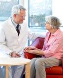 Médico que consulta con una mujer mayor Imagen de archivo libre de regalías