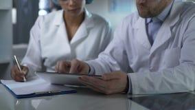 Médico que da instrucciones al ayudante, comprobando resultados de la prueba en la tableta almacen de video