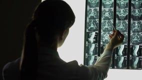 Médico que diagnostica problemas com parte traseira, imagem do raio X que revela a doença séria filme