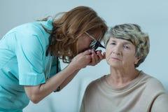 Médico que examina a la mujer mayor imagen de archivo libre de regalías