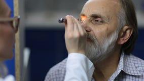 Médico que examina o reflexo pupillary com lanterna elétrica video estoque
