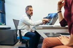 Médico que explica resultado de la radiografía al paciente foto de archivo