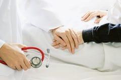 Médico que lleva a cabo las manos pacientes del ` s y que la conforta con cuidado imágenes de archivo libres de regalías