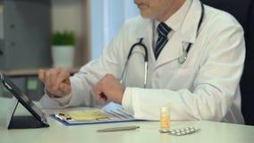 Médico que mira el boletín de inscripción, tratamiento que prescribe en línea, consultor metrajes