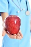 Médico que muestra la manzana Fotos de archivo libres de regalías