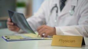 Médico que olha o raio X dos pulmões e que prescreve a medicamentação ao paciente no escritório video estoque