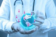 Médico que sostiene un globo del mundo en sus manos Foto de archivo libre de regalías