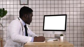 Médico que toma as notas que olham acima a informação em seu computador Indicador branco foto de stock royalty free