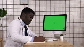 Médico que toma las notas que miran para arriba la información sobre su ordenador Visualización blanca metrajes