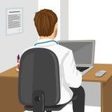 Médico que usa el ordenador portátil en clínica Imagenes de archivo