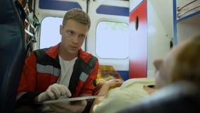 Médico que usa la tableta para hacer expedientes electrónicos sobre paciente en ambulancia almacen de video