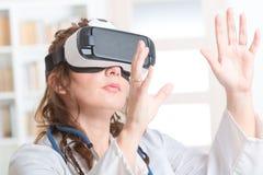 Médico que usa las auriculares de la realidad virtual Imagen de archivo