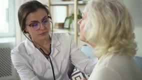 Médico que usa a mulher superior da visita do estetoscópio em sua casa filme